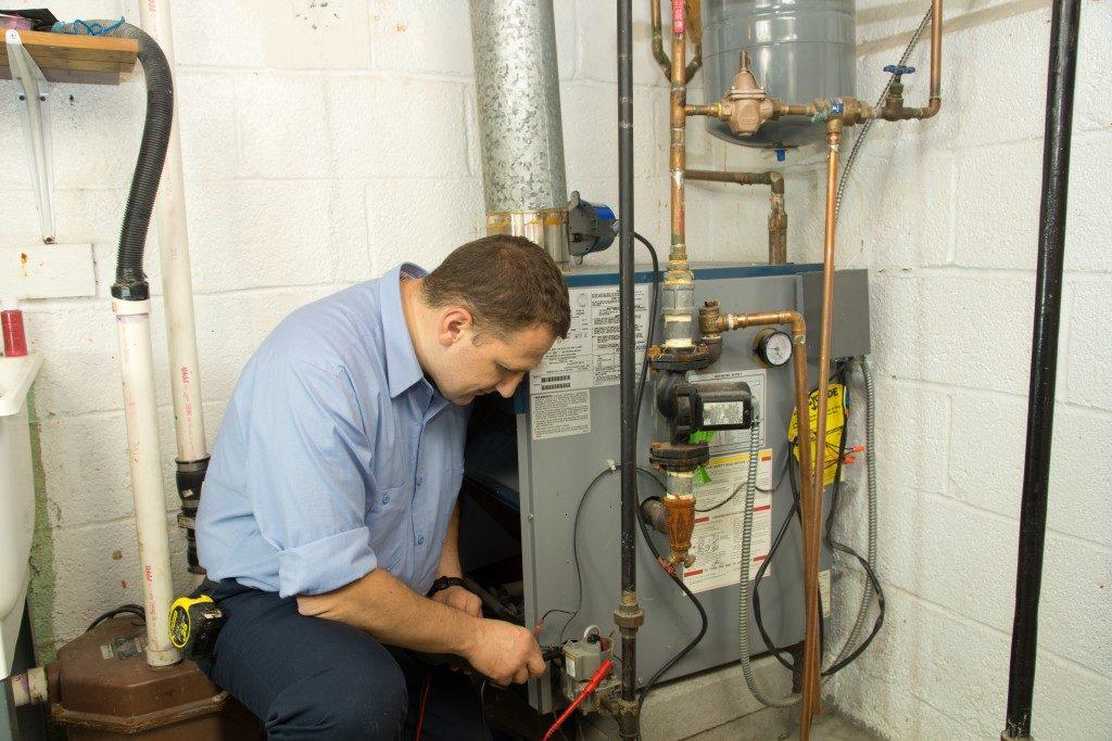 Plumber fixing the gas furnace