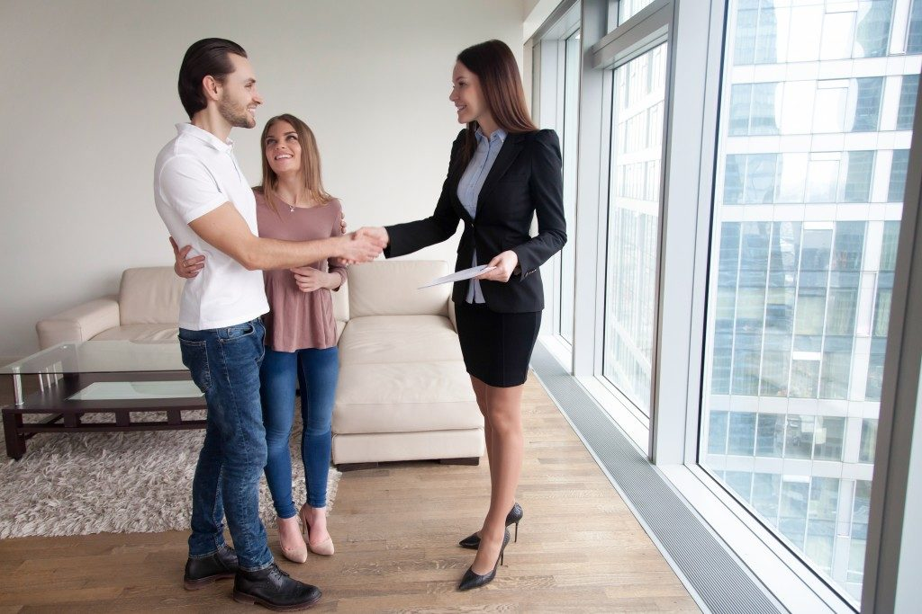 real estate broker showing apartment to couple