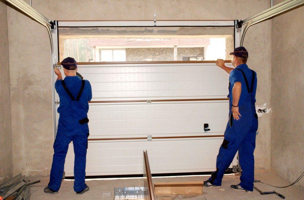 professionals measuring garage door