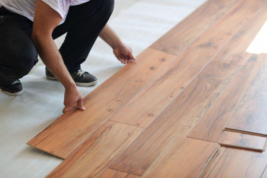 a man installing a wood flooring