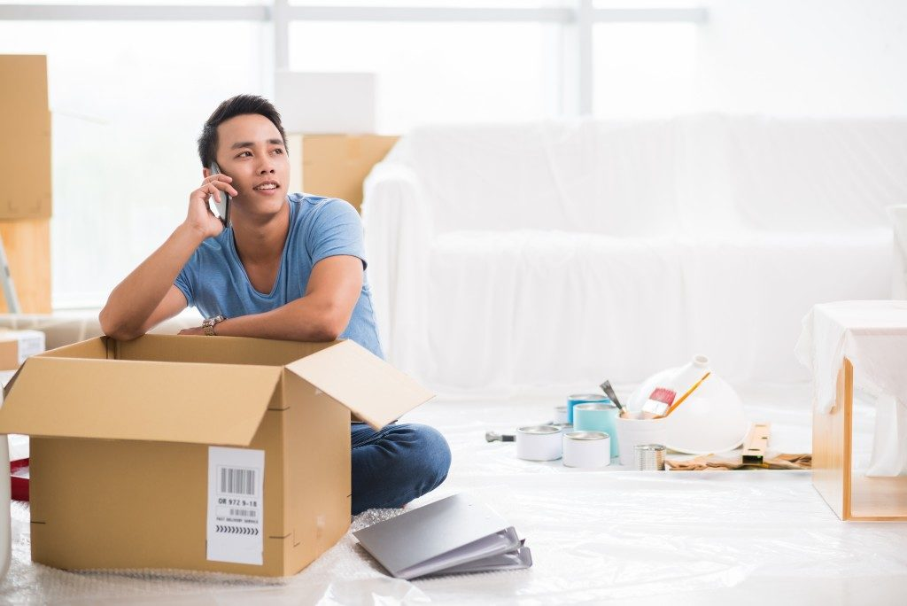 man on hs phone while packing stuff