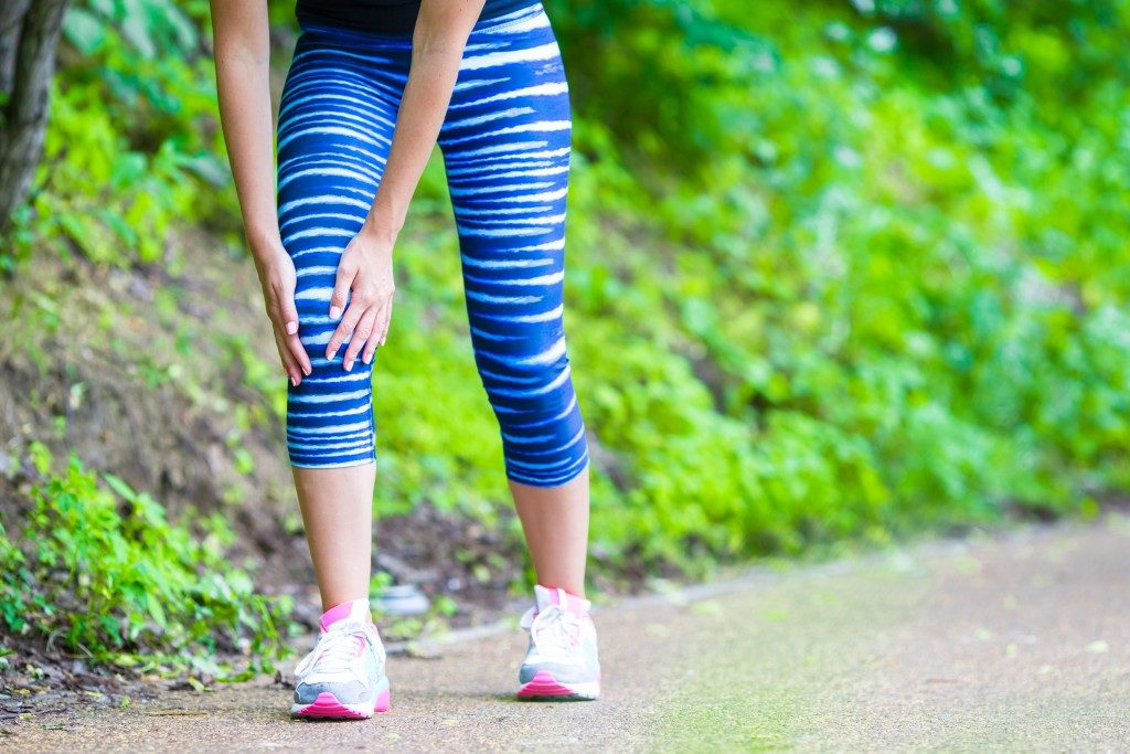 Woman with a hurting knee while jogging