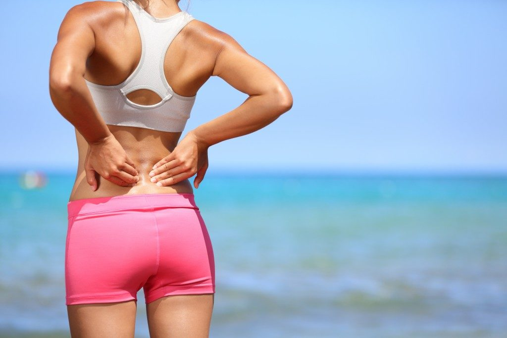 Woman experiencing back pain while running