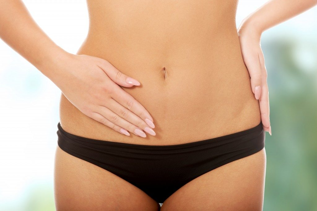 woman touching her lower abdomen